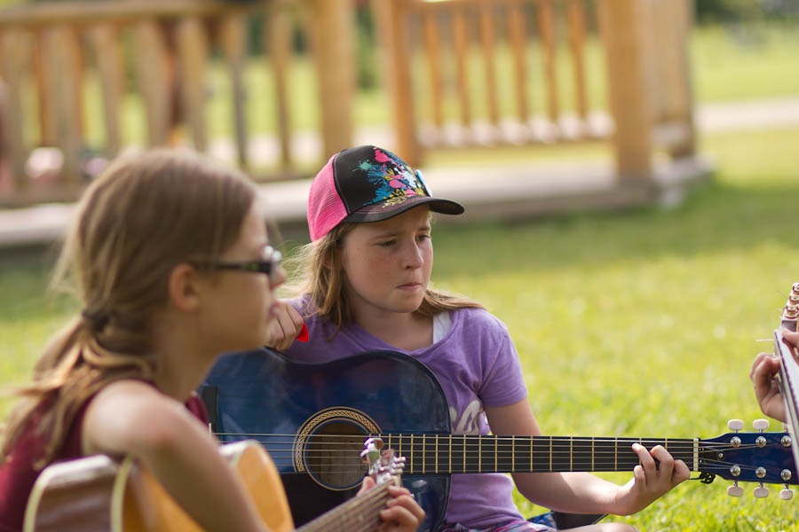 Two campers sitting side by side playing guitar at summer camp.