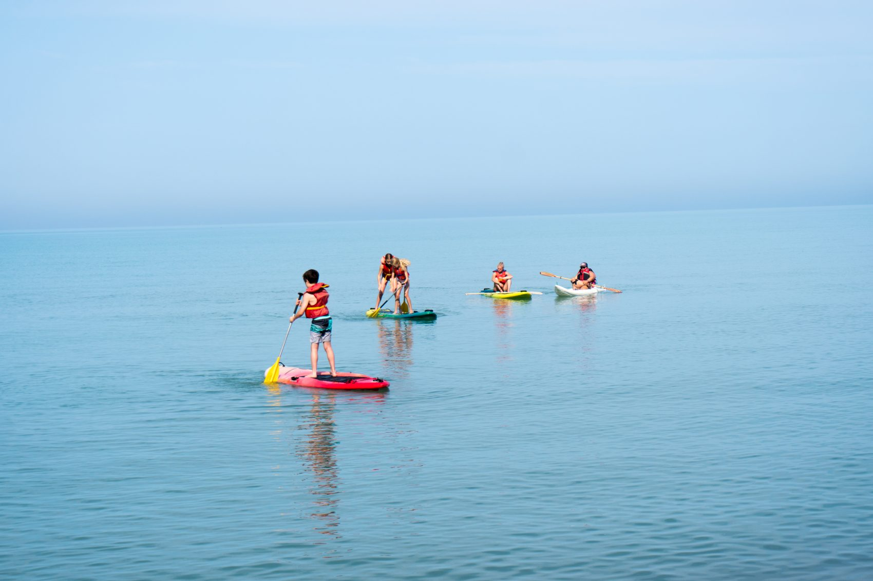 Four campers are seen standing on paddle boards on Lake Huron.