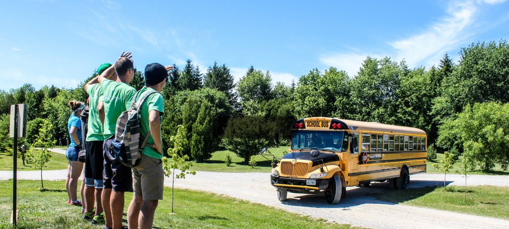 Summer camp staff stand on a hill waving to a bus as it goes to exit the site.