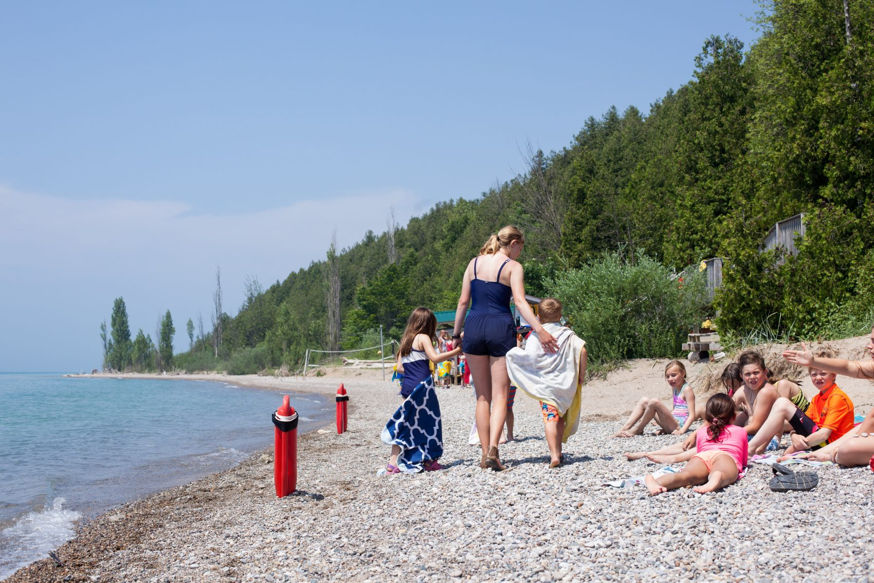 A staff member with two campers standing all holding hands walking down Lake Huron beach.