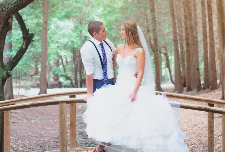 A bride and groom look at one another smiling, standing on a wooden bridge over a small rock creek in the cedar forest.