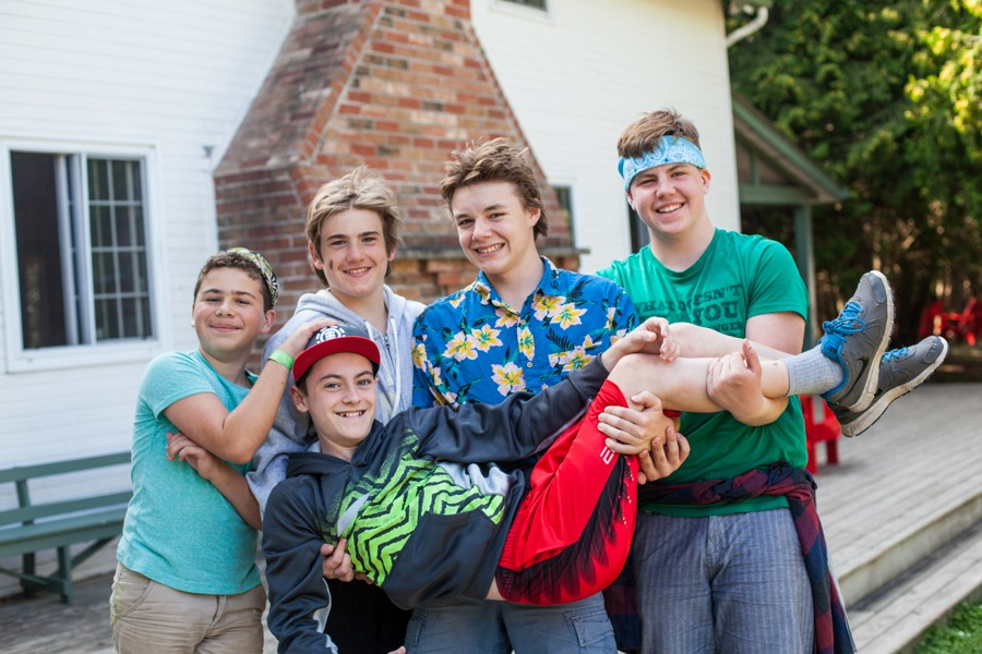 four smiling teen campers holding up their friend in front of Harmony House