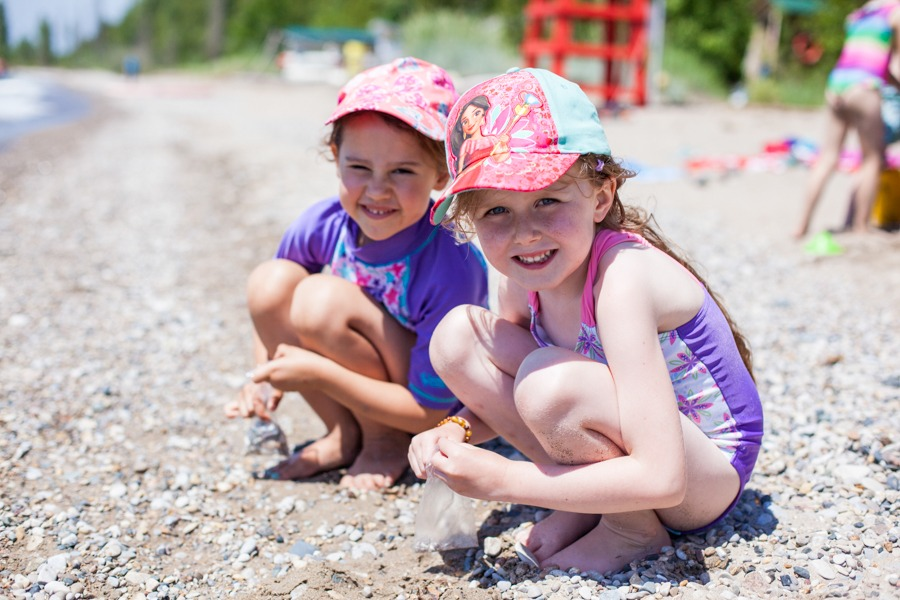 Two smiling young campers crouch to collect rocks on the Kintail beach