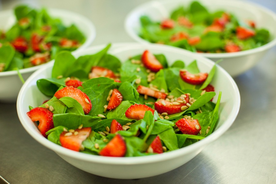 Fresh strawberry and spinach salad with sunflower seeds are in bowls on the kitchen counter.