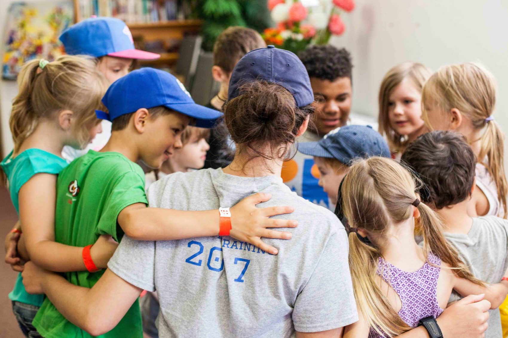 Staff and campers gather in a circle wrapping their arms around one another.