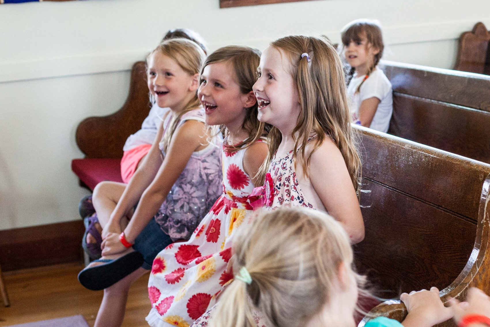 Three young campers look to the left smiling and laughing while sitting on church pews.