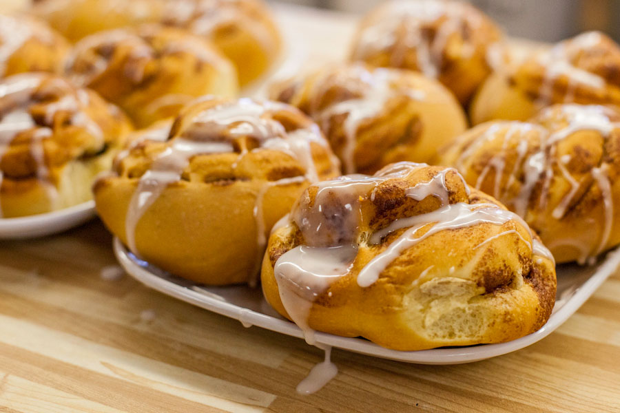 Freshly glazed cinnamon buns are on a tray on the kitchen counter.
