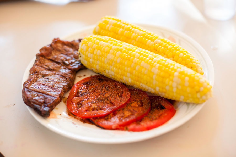 Steak, tomato slices with balsamic drizzle, and two corn on the cob on a white dinner plate on a table.