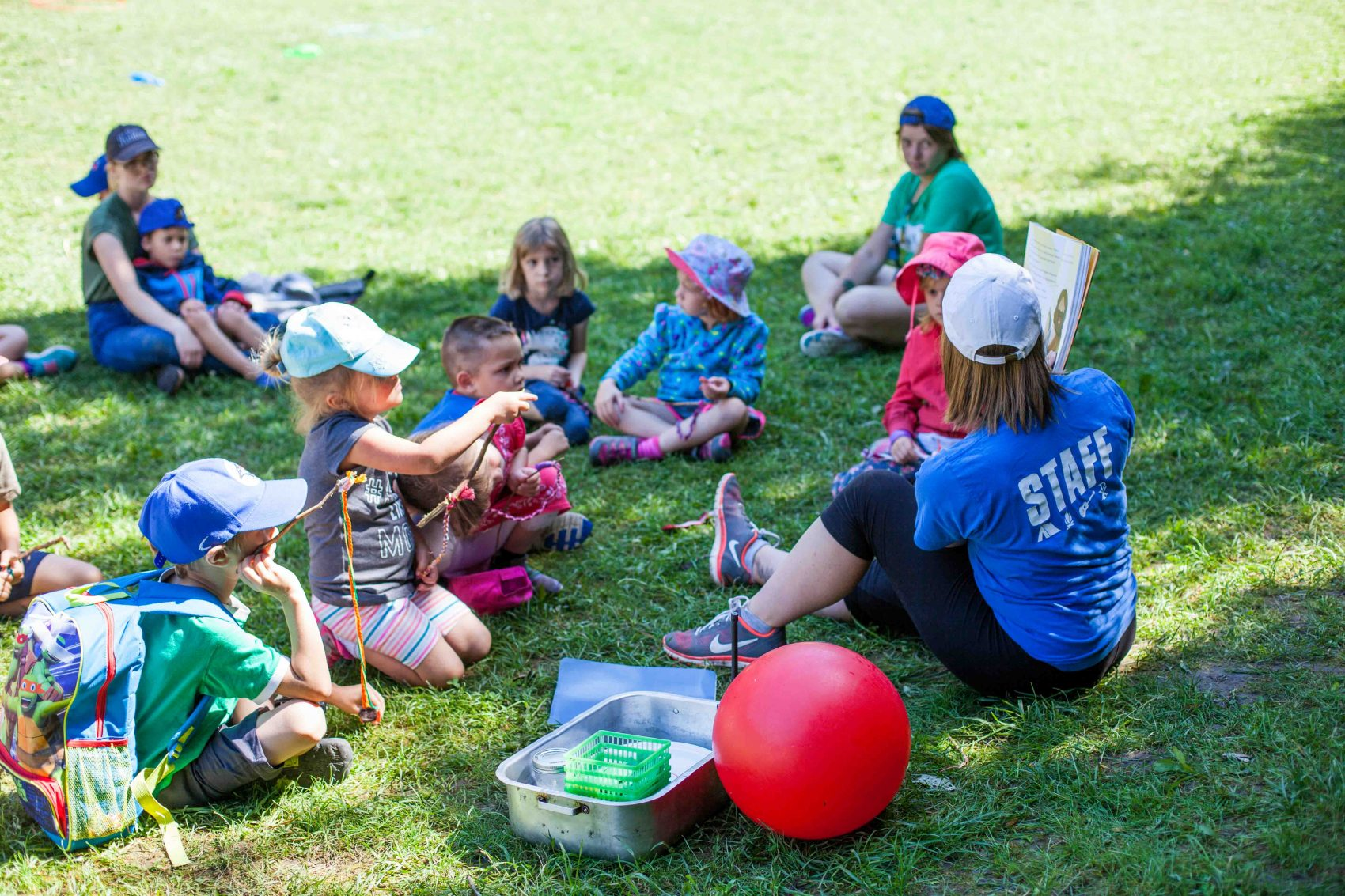 A staff member holds open a Spark bible and is reading a page to a group of young campers sitting on the grass.