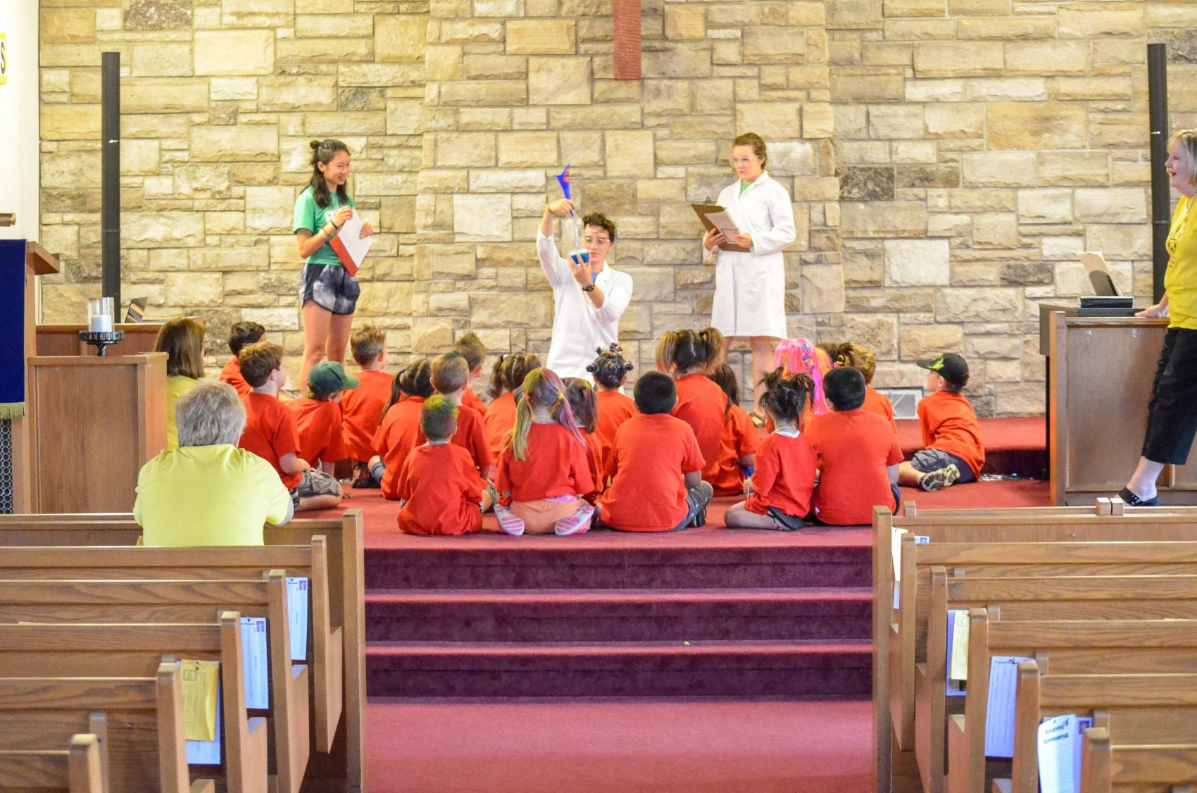 A group of children with bright orange t-shirts sit onstage at a church while three adults stand amongst them acting out a skit.