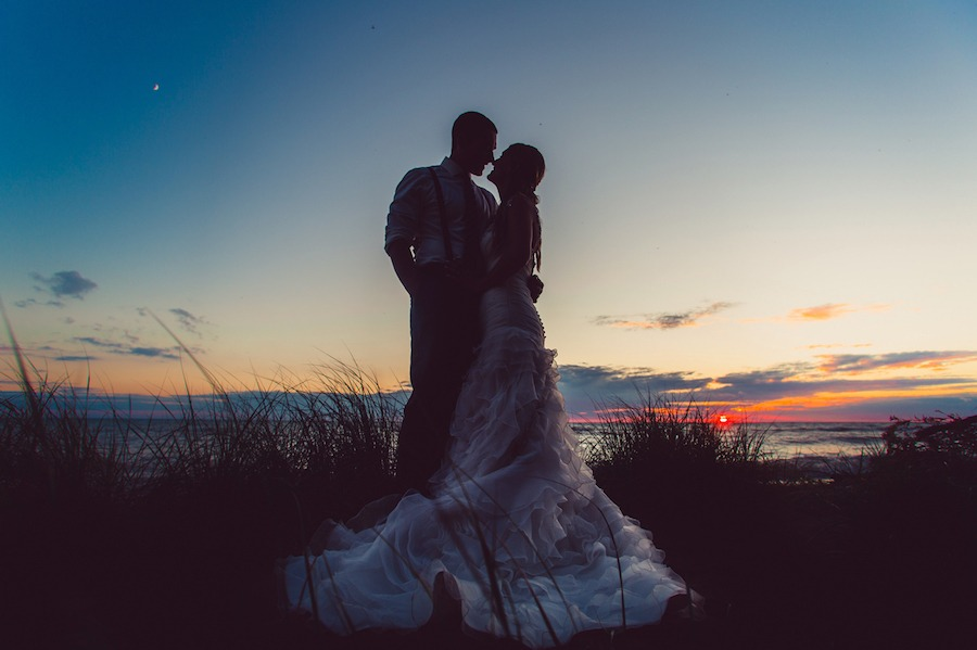 A silhouette of a bride and groom captured on the shores of Lake Huron as the sun is almost set in behind them.