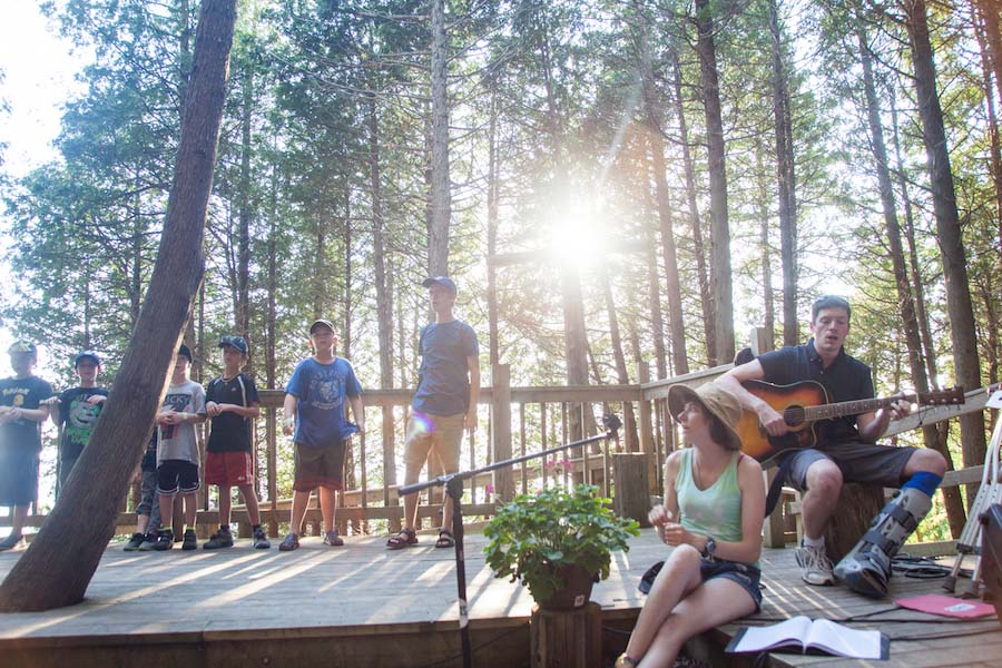 Staff and campers are onstage at the Outdoor Chapel with two people to the right playing guitars.