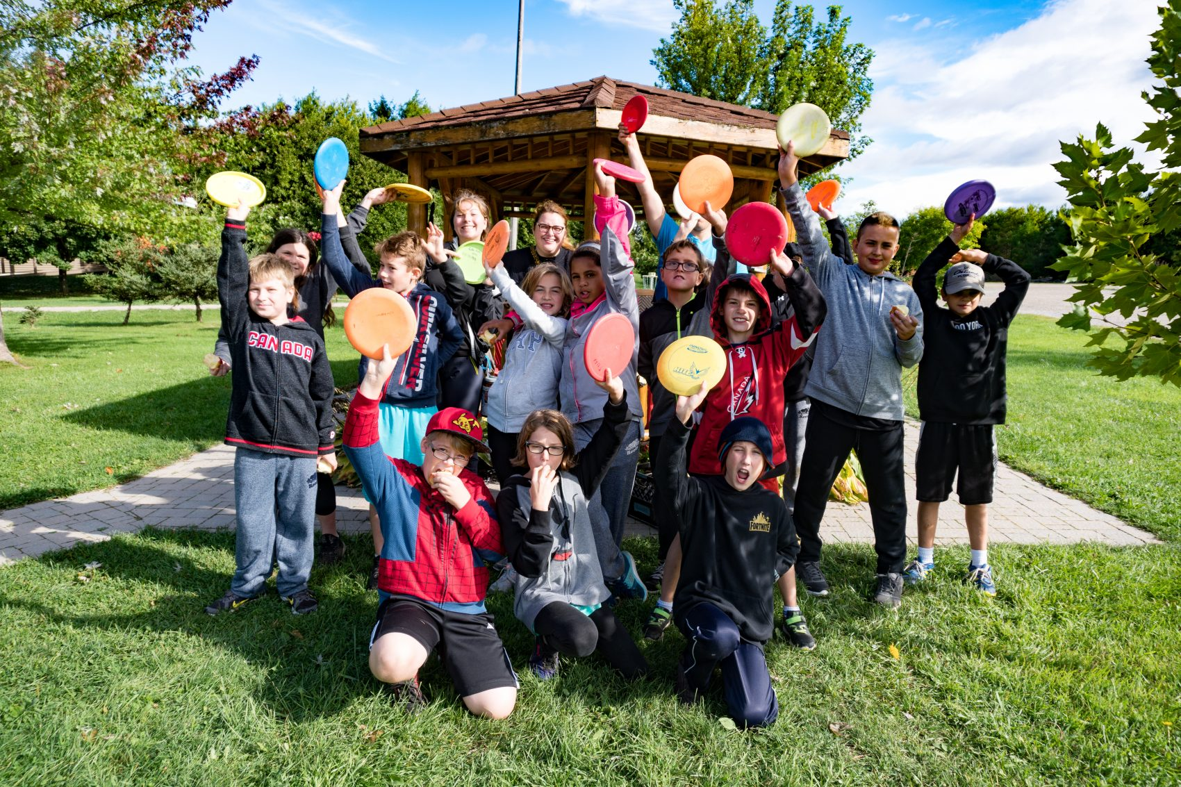 A group of staff and campers are posing in front of a gazebo holding up their discs from disc golf programming at summer camp.