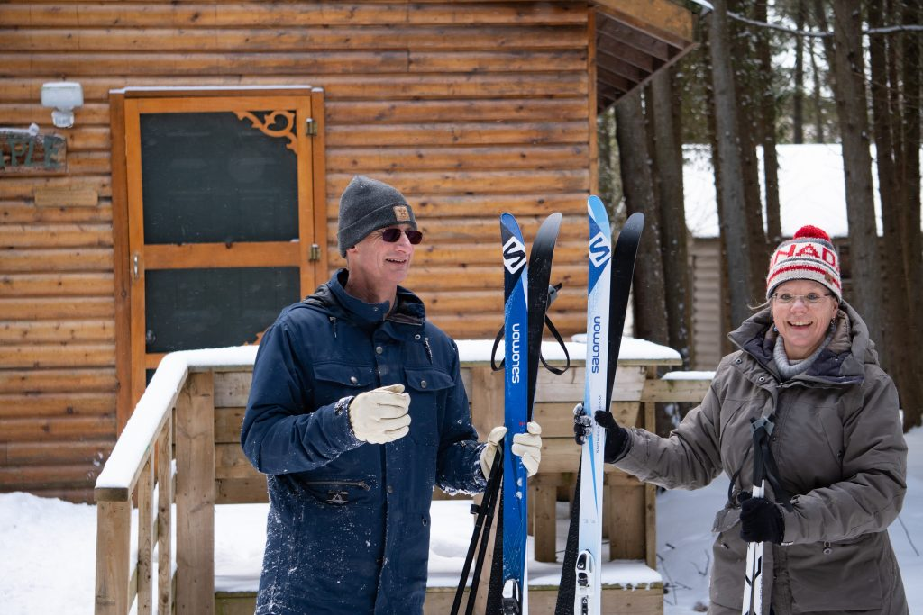 Two adults dressed in winter wear holding skis outside of a cabin at Camp Kintail.