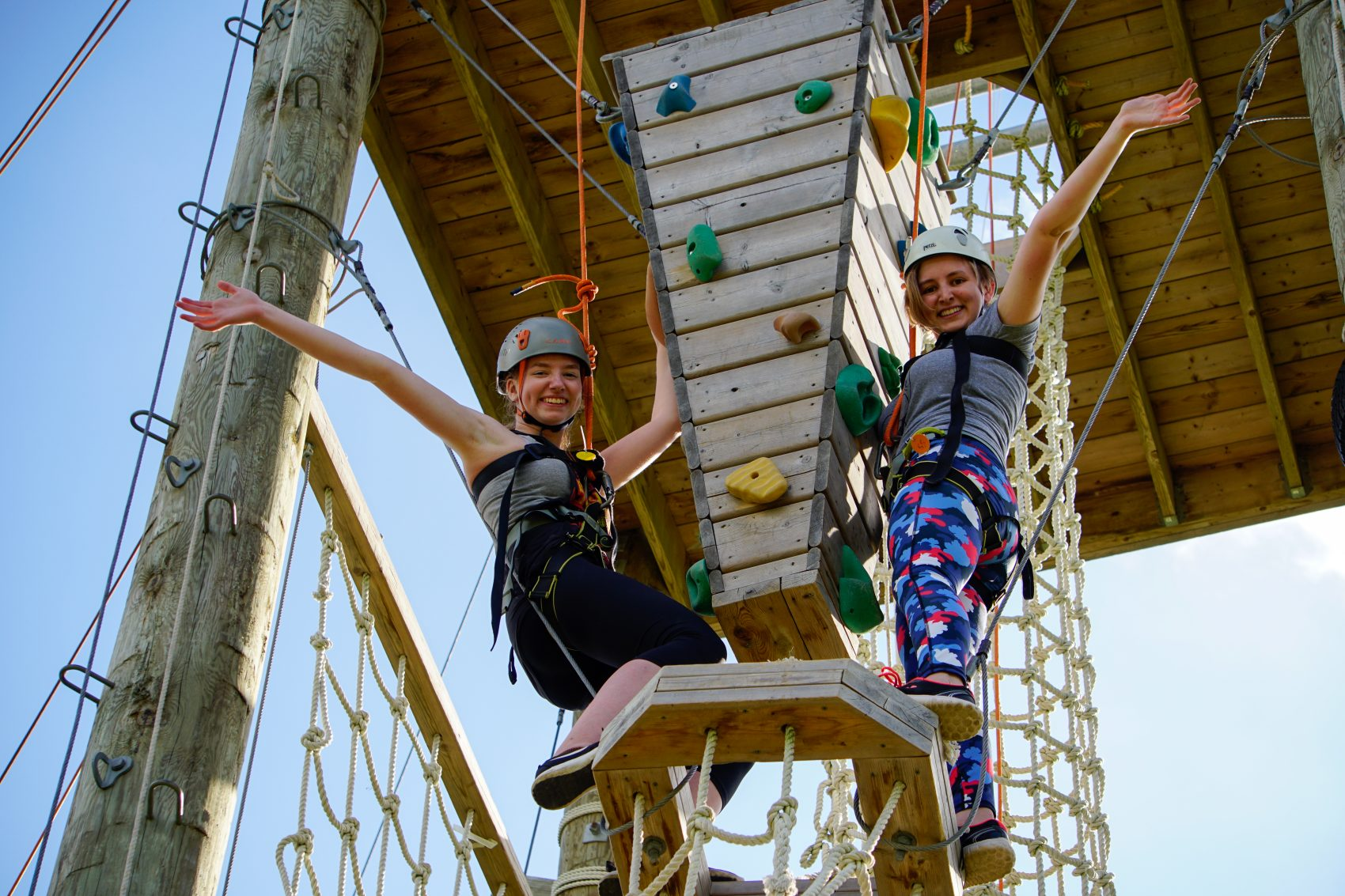 Two campers stretch their arms out in the air as they complete their climb on the adventure tower at Camp Kintail.