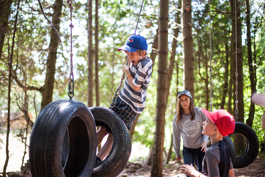 """A young male camper swings on a tire while working to complete the low rope element """"Tire Traverse"""" at Camp Kintail."""