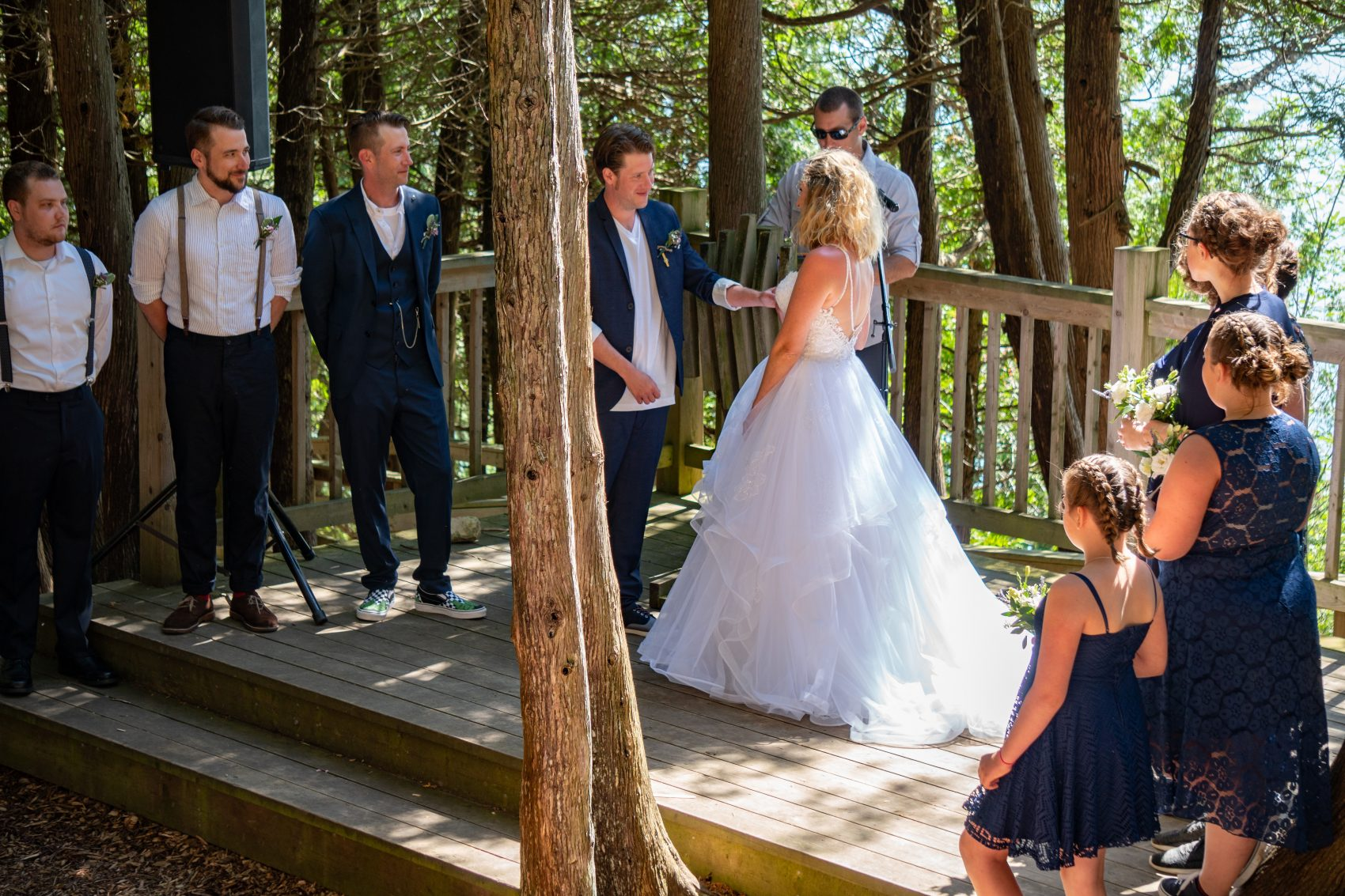 A wedding couple surrounded by their wedding party and officiant are on the stage of the Outdoor Chapel in the midst of their wedding ceremony.