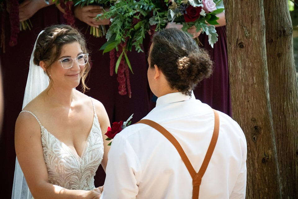 A bride and groom hold hands and look into each others eyes during their wedding ceremony in the Outdoor Chapel at summer camp. The groom's back is facing us but we can see the bride's face, she is smiling.
