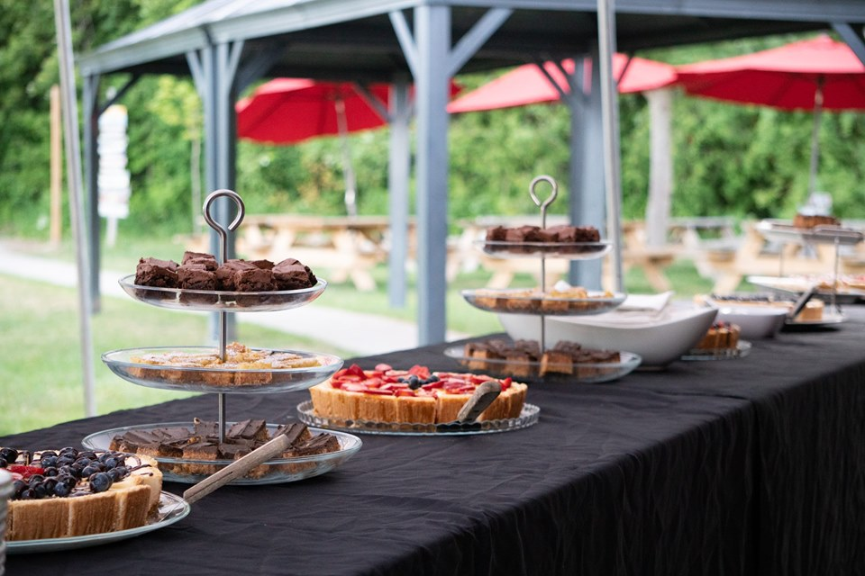 A dessert buffet dressed with black linens that has various trays holding assorted squares and cheesecakes.