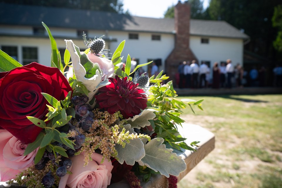 A bouquet of flowers with red and pink roses. Harmony House with wedding guests outside mingling on the deck is seen in the background.