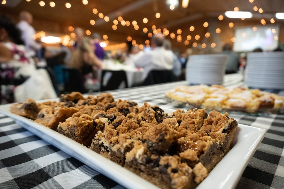 S'mores bar squares are on a white glass tray on a buffet table dressed with a black and white checkered tablecloth.