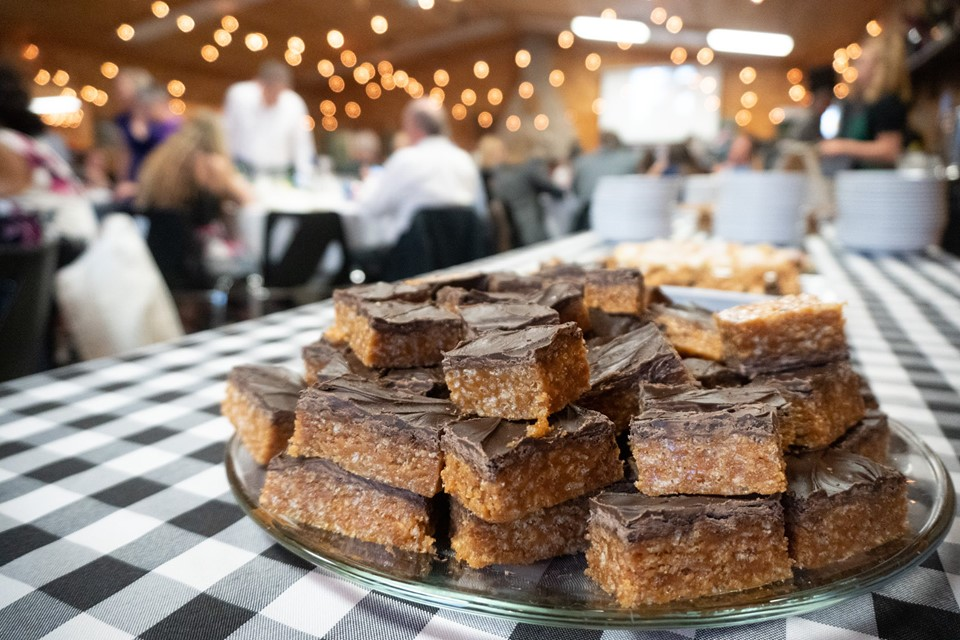 Sweet Marie squares are on a platter, on a buffet table that is dressed with a black and white checkered tablecloth.