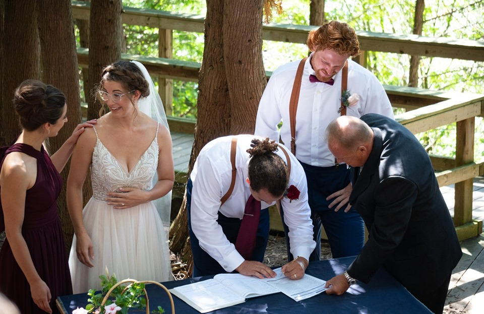 A bride and groom along with their best man, maid of honour, and officiant are at a table on the stage in the Outdoor Chapel where the wedding couple is smiling as they sign their wedding license.