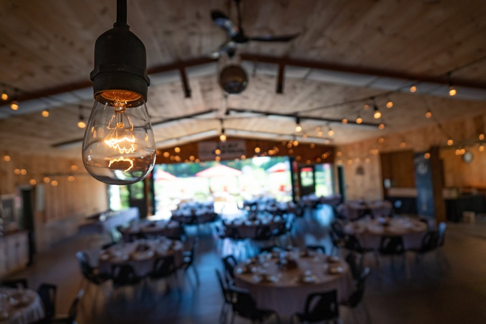 A scenic view of MacDonald Lodge set up with Edison lights overhead and circular wedding tables dressed with white linens and glassware. The lodge is lit up from the Edison lights and accordion doors at the back that are fully opened.