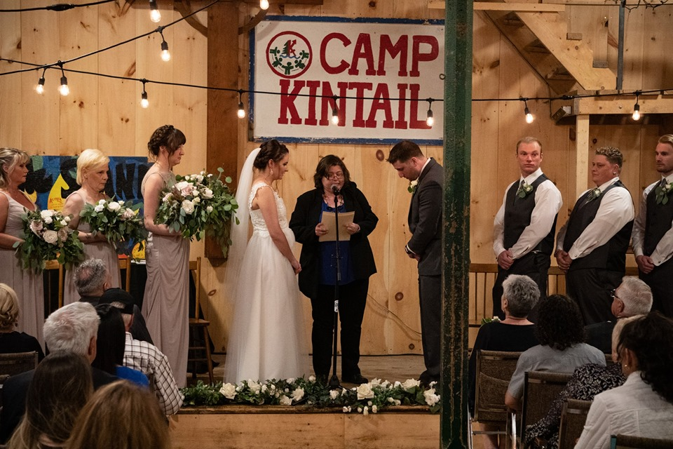 A wedding couple with their wedding party and officiant stand on a stage inside the Rec Hall for their wedding ceremony.