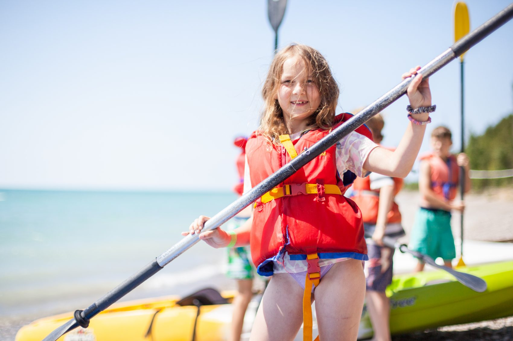 A camper smiling with a kayak paddle held in their two hands standing on the shore of Lake Huron.