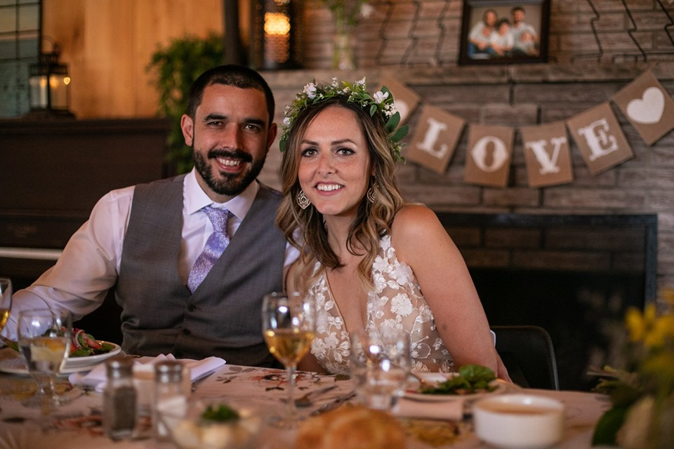A bride and groom seated at their head table in MacDonald Lodge in front of an indoor wood burning fireplace smile at the camera.