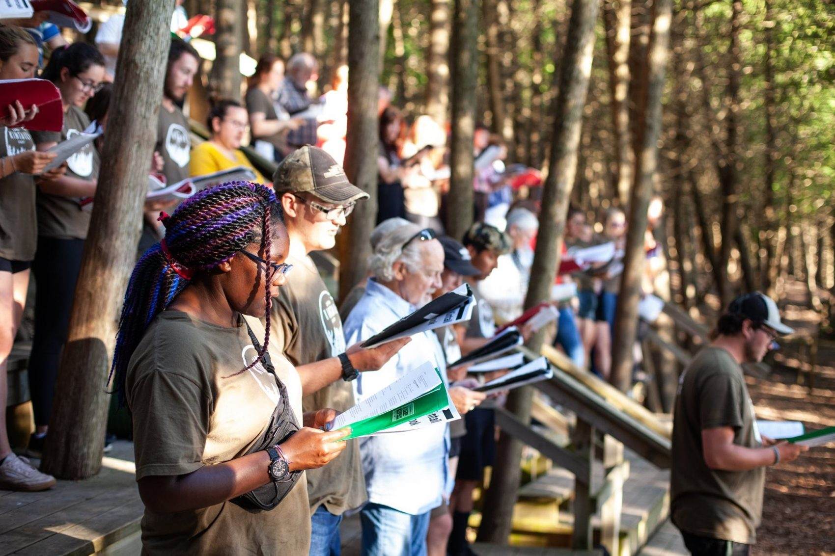 A group of adults standing in theatre seating are reading and singing out of songbooks in the Outdoor Chapel at summer camp.
