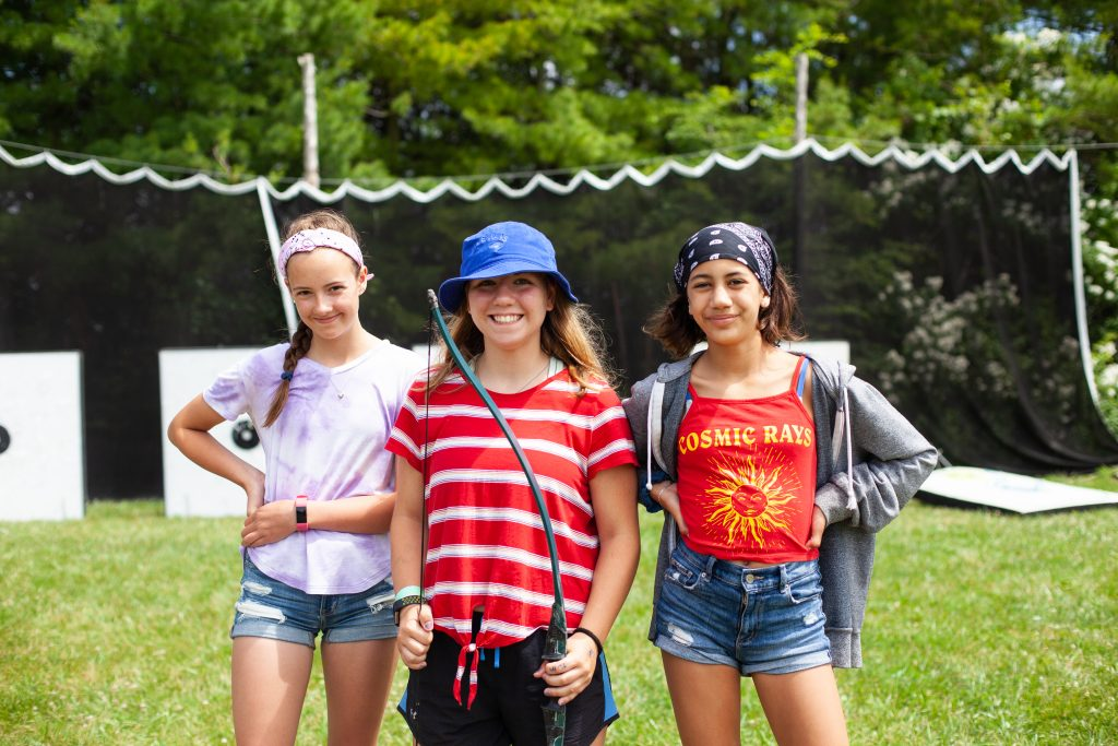 Three campers are smiling at an archery range. The camper in the middle is seen holding a bow. Archery targets and a net are seen in the background.