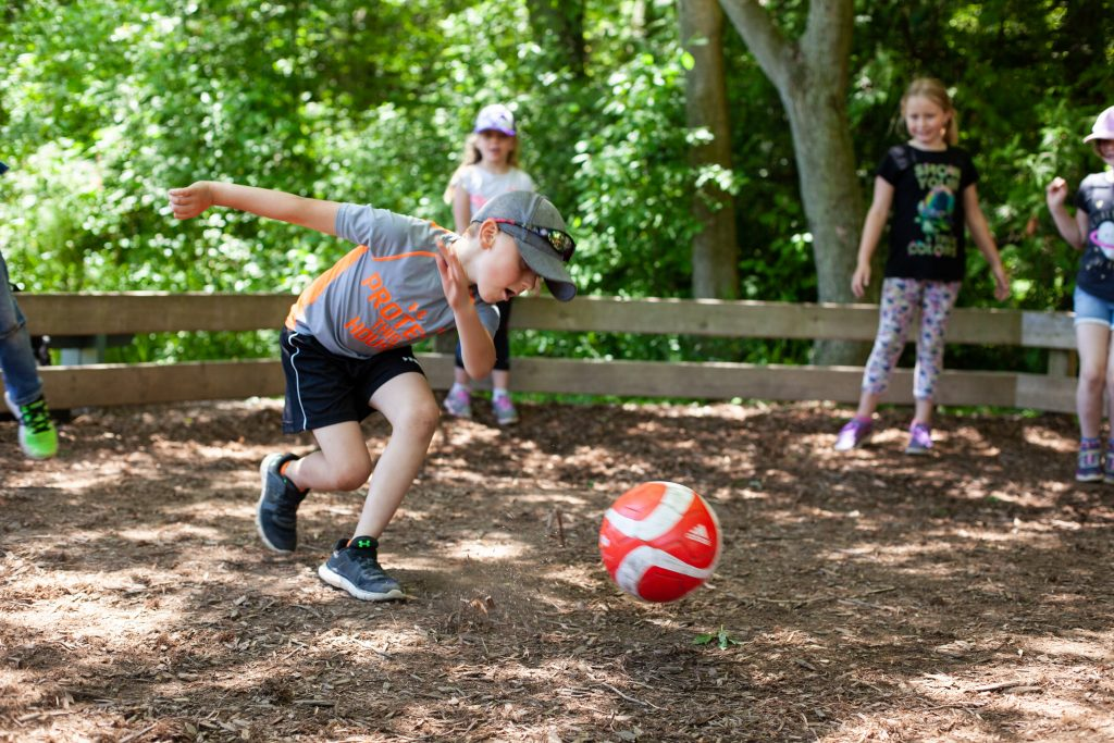 Campers are playing gaga-ball at summer camp. A young camper prepares to hit the ball in attempt to get another camper out out the game.