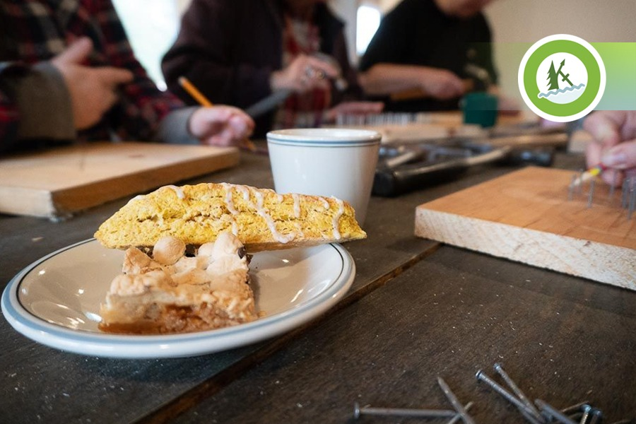 A pumpkin scone and s'mores square on a plate with people sketching a design on pieces of wood in the background.