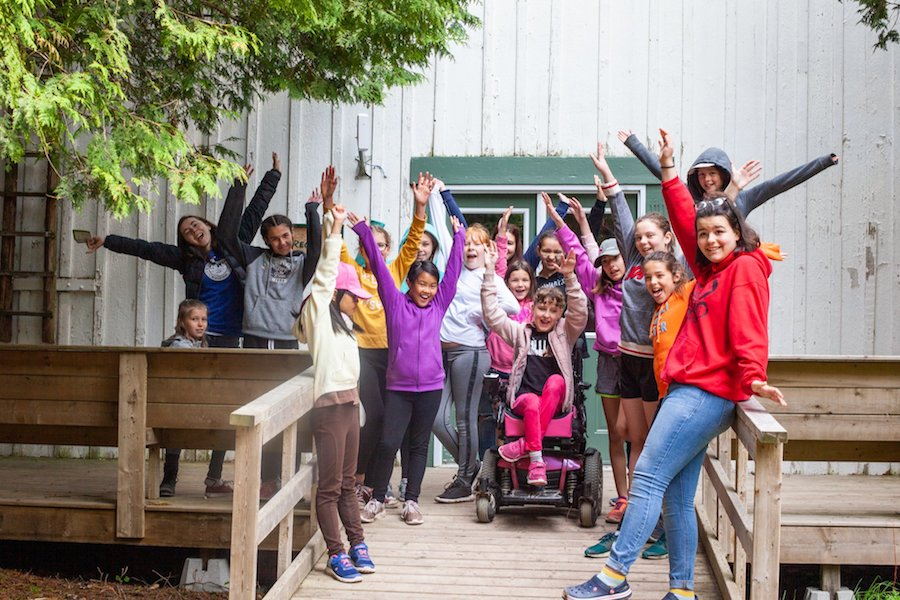 a large group of campers and staff smiling with raised hands on the porch of the Kintail Rec Hall
