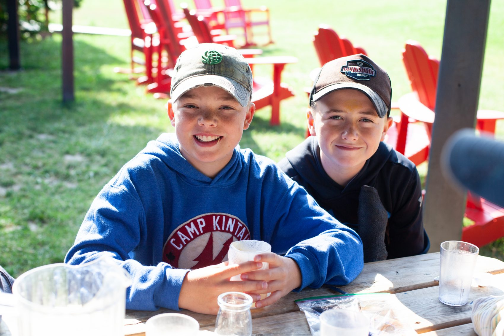 Two male campers sit smiling at a picnic table with their materials needed for banana DNA extraction.