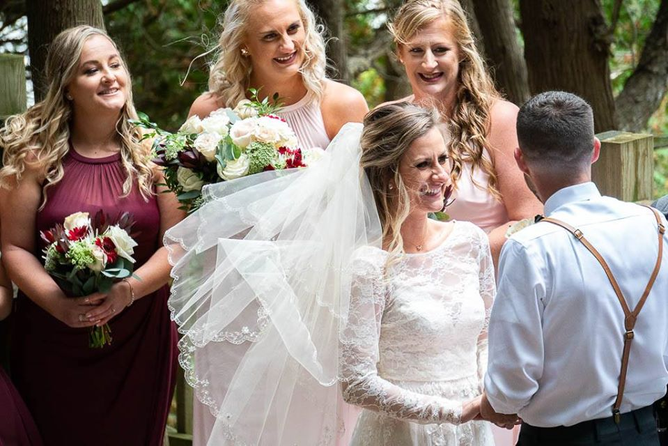 A bride is seen smiling as she hold's the groom's hands, his back to us, with her bridesmaids behind her also smiling. They are on the stage of the Outdoor Chapel with their hair and dresses blowing in the wind coming off of Lake Huron.