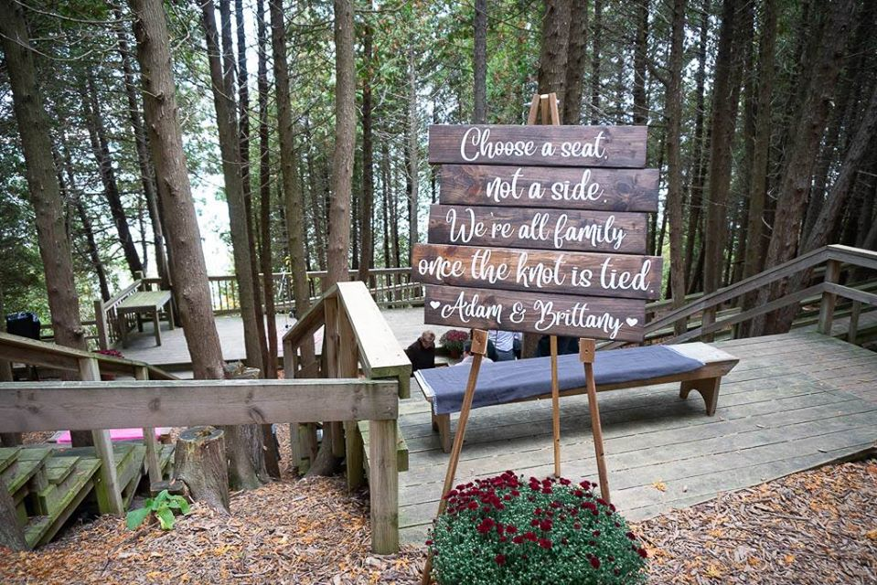 """A wedding sign at the top of the Outdoor Chapel reads, """"Choose a seat, not a side, we're all family, once the knot is tied, Adam and Brittany""""."""