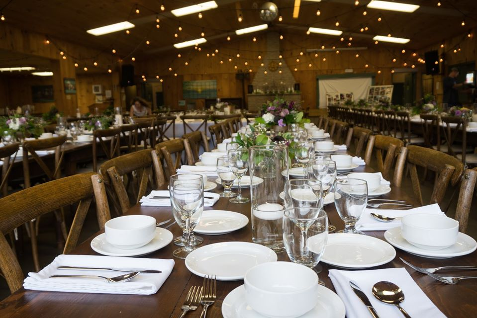Brown wooden chairs and harvest tables dressed with glassware and white napkins inside MacDonald Lodge dining hall.