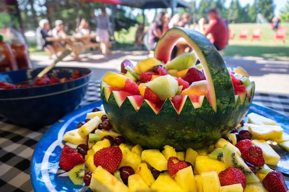 Fresh seasonal fruit is placed in a watermelon carved basket on a tray on a buffet line with guests enjoying summer camp in the background.
