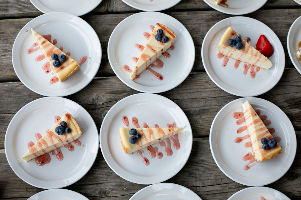 Overhead shot of cheesecake on plates that are dressed with strawberry drizzle, blueberries, and strawberries.
