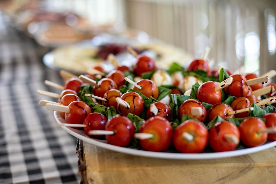 Caprese skewers with balsamic drizzle are on a wooden platform that is on top of a buffet table that is dressed with a checkered tablecloth.