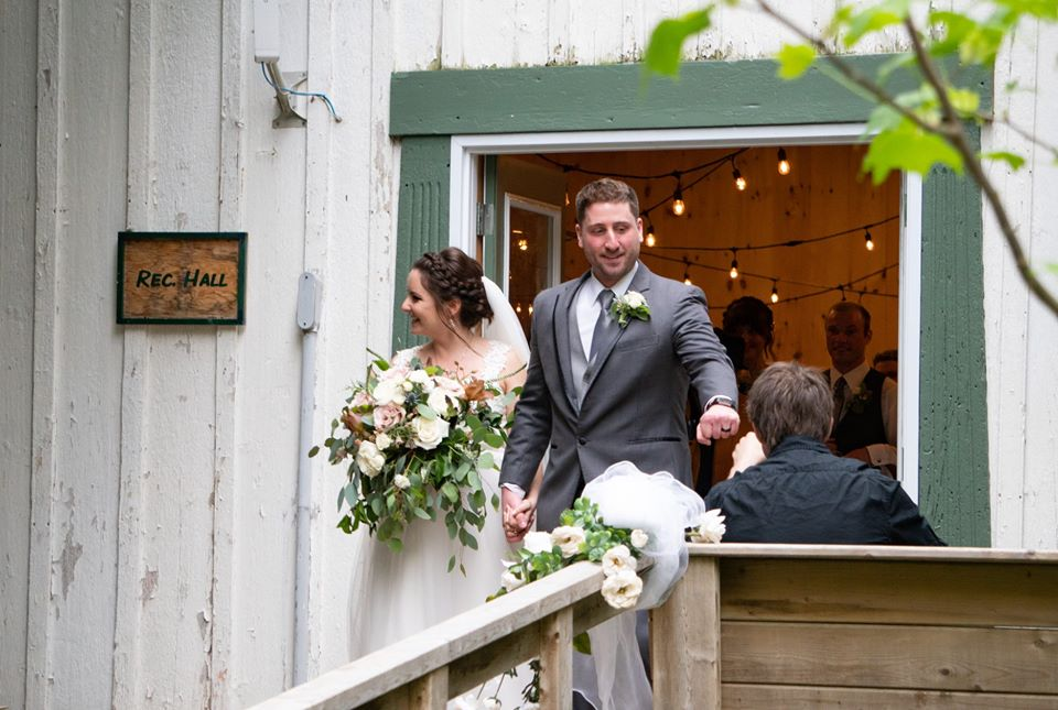 A bride and groom are exiting the Rec Hall smiling and holding hands, just married at summer camp.