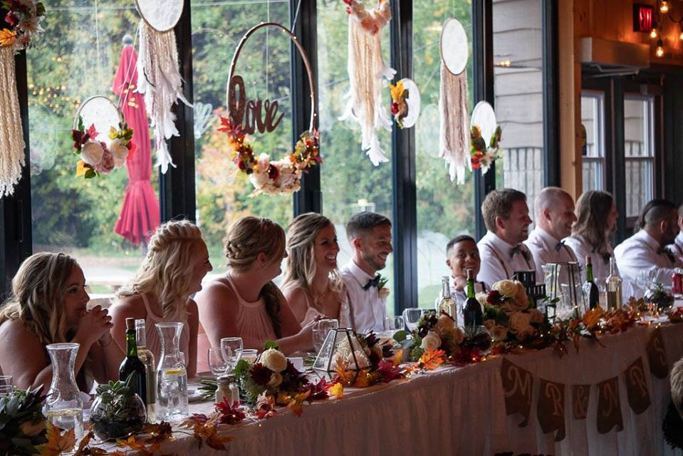 A wedding couple and party is seated at the head table smiling. They are back lit from the accordion door windows behind them.