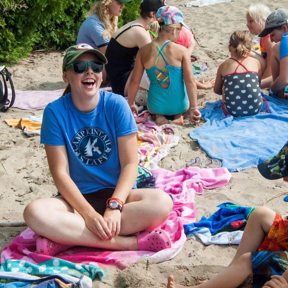 A staff member named Lani is laughing and smiling on the beach on Lake Huron.
