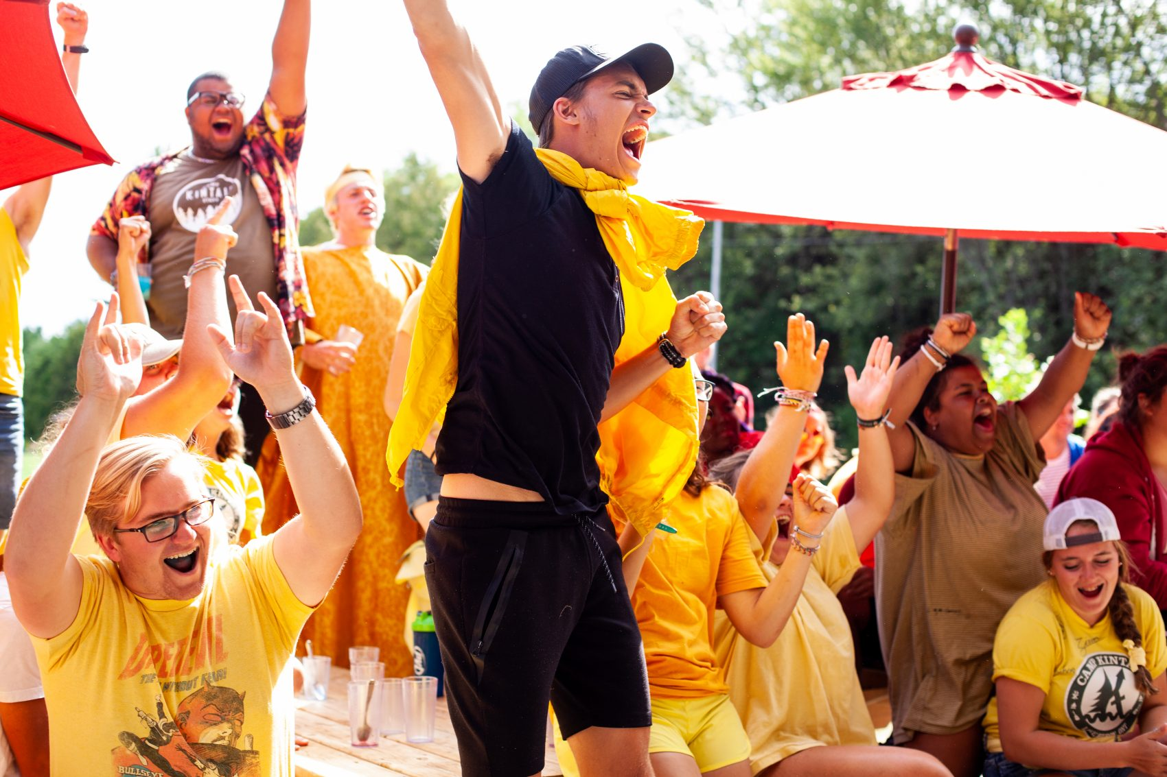 Staff members dressed in yellow chant, scream, and cheer enthusiastically at summer camp!