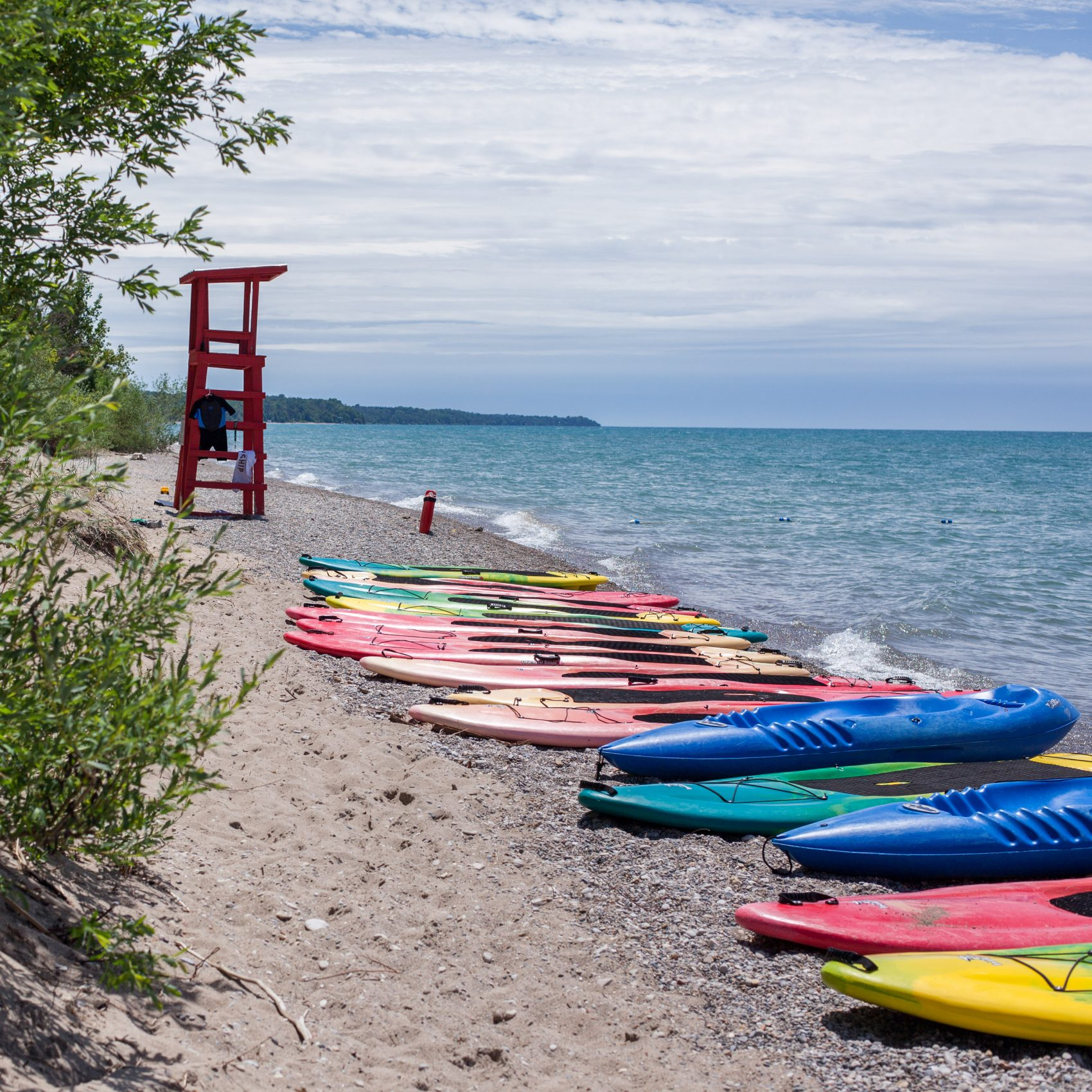 A scenic view of kayaks and paddle boards resting on the sandy shores of Lake Huron.