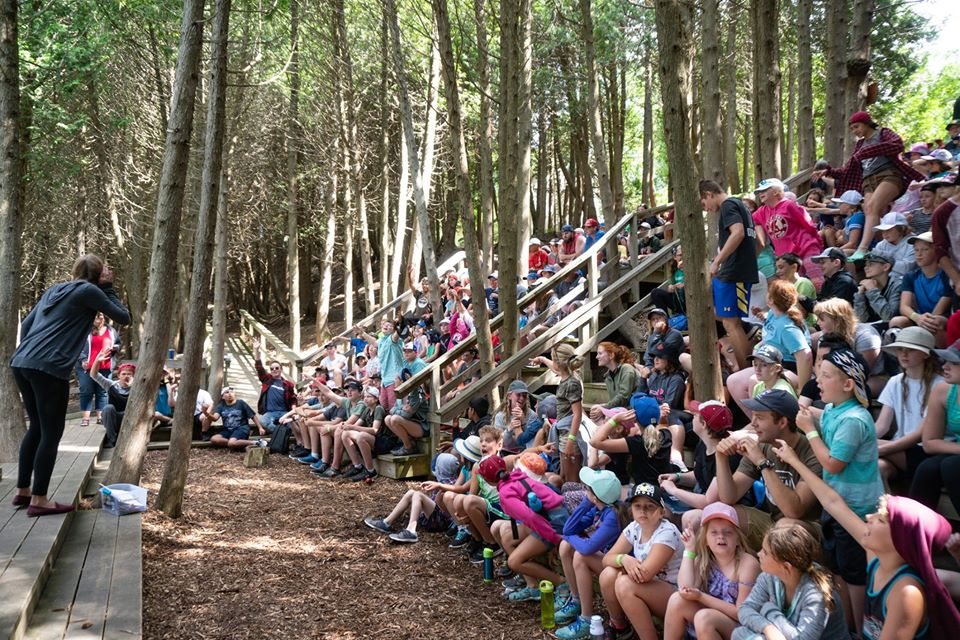 A group of staff and campers sit in theatre seating at the Outdoor Chapel, listening to the person standing on the stage.