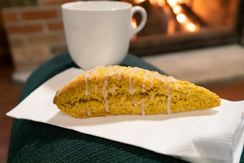 A pumpkin scone on a white napkin next to a cup of coffee. A indoor fire in the fireplace can be seen in the background.